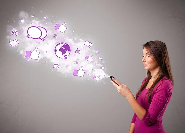 Pretty young girl holding a phone with social media icons in abstract cloud-1